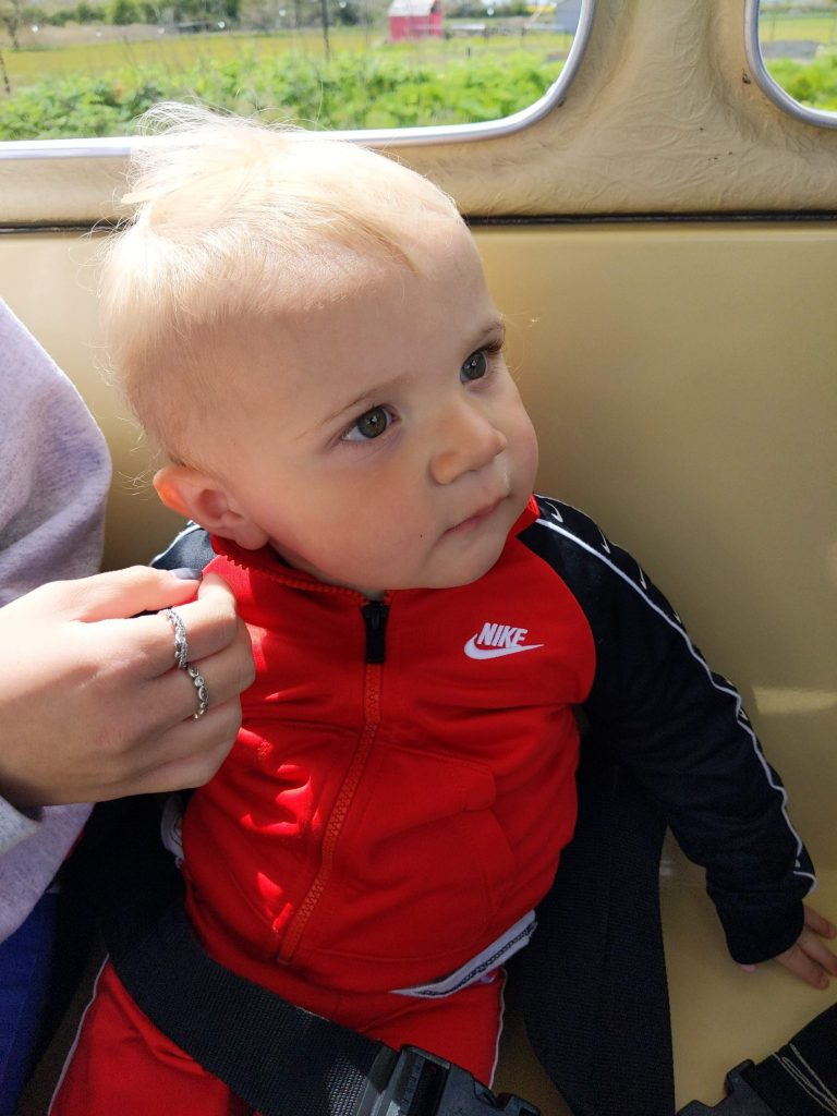 Keaton (male toddler) close up of face sitting on a train