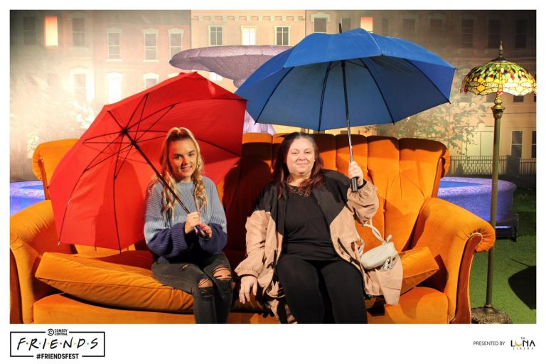 Mother and daughter on the orange sofa holding umbrellas like the title opening of the show Friends