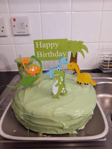 A birthday cake decorated in green icing with dinosaurs on top