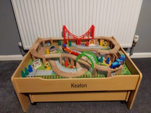 A train set on a wooden table with the name Keaton engraved